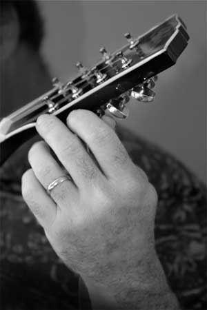 Tuning up! Closeup of a man's hand tuning a mandolin