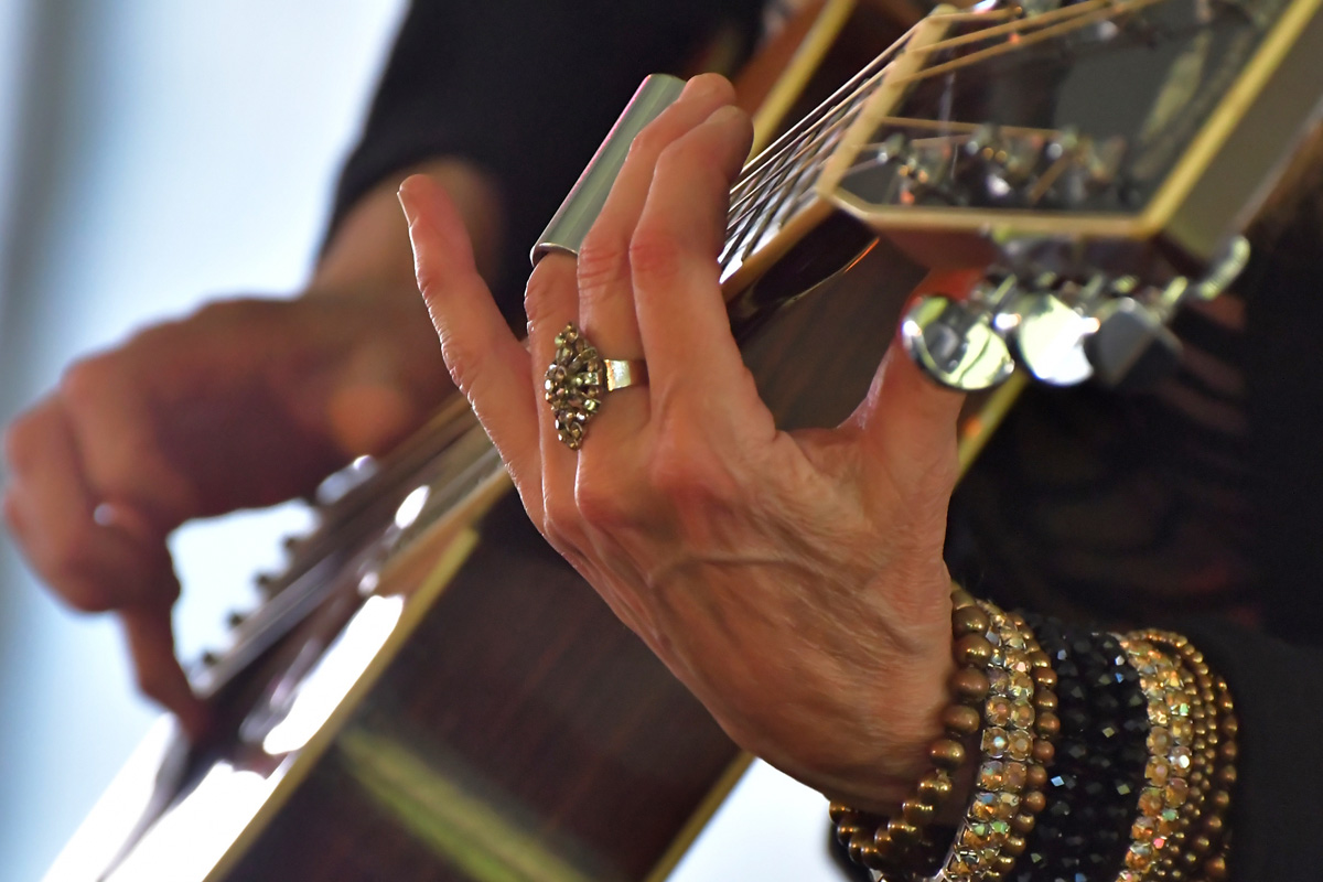 large decorative image: closeup of a woman's hands playing blues guitar, wearing lots of sparkly bracelets and using a silver slide.